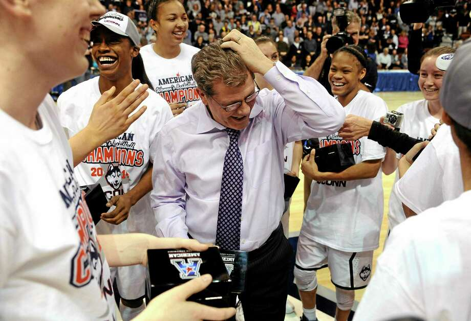 UConn head coach Geno Auriemma fixes his hair after his team messed it up after winning the American Athletic Conference tournament championship game 72-52 over Louisville on Monday in Uncasville. Photo: Jessica Hill — The Associated Press   / FR125654 AP