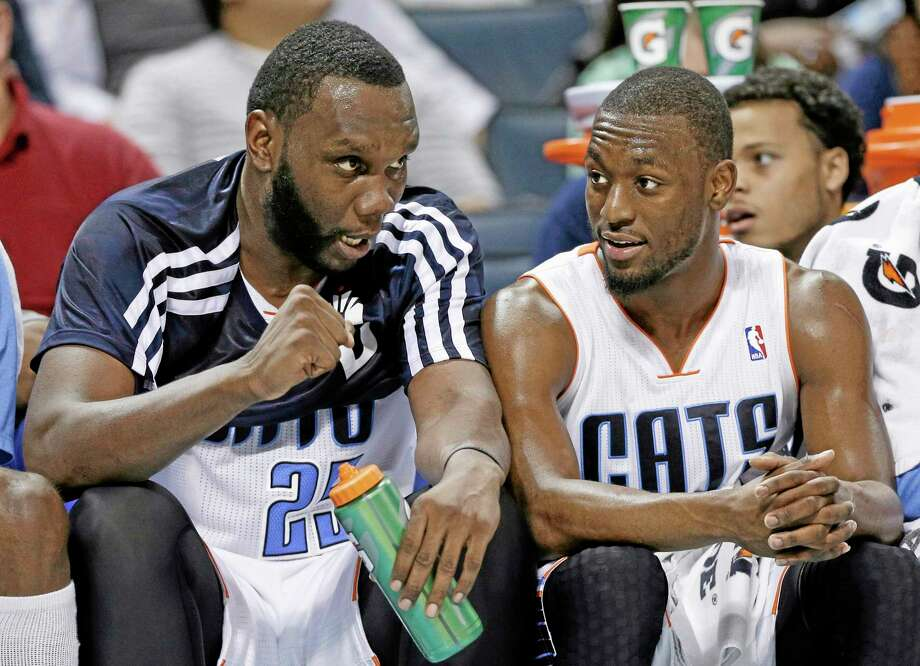 The Charlotte Bobcats' Al Jefferson, left, and former UConn All-American Kemba Walker, right, celebrate on the bench during the second half of Tuesday's 108-98 win over the Knicks. Photo: Chuck Burton  — The Associated Press   / AP