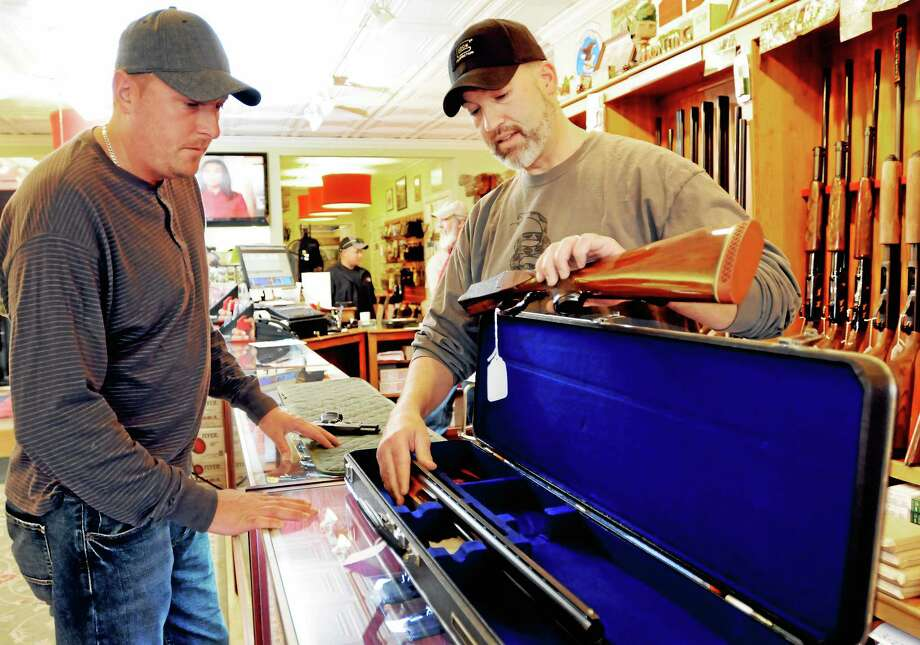 John Gray of East Haven, left, admires a competition Winchester 101 double-barreled shotgun Friday, May 9, 2014, shown by Mike Higgins, co-owner of TGS Outdoors gun shop in Branford. Photo: (Peter Hvizdak — New Haven Register) / ©Peter Hvizdak /  New Haven Register