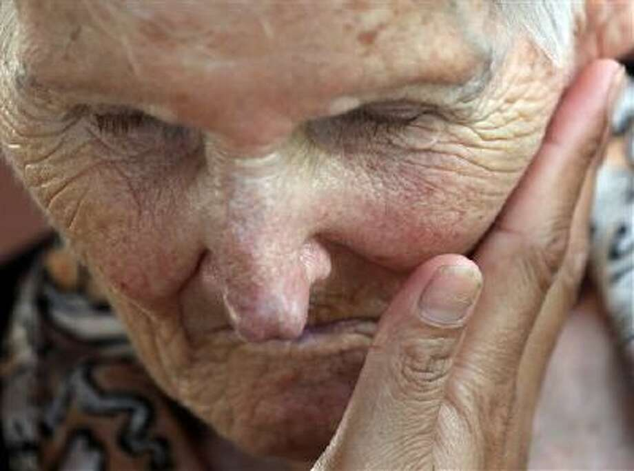 A Thai caretaker gently massages the face of Loulou, a 91-year-old Alzheimer patient from Switzerland, while relaxing at Baan Kamlangchay care center in Chiang Mai province, northern Thailand. Thailand is poised to attract more Alzheimer's sufferers. Photo: AP / AP