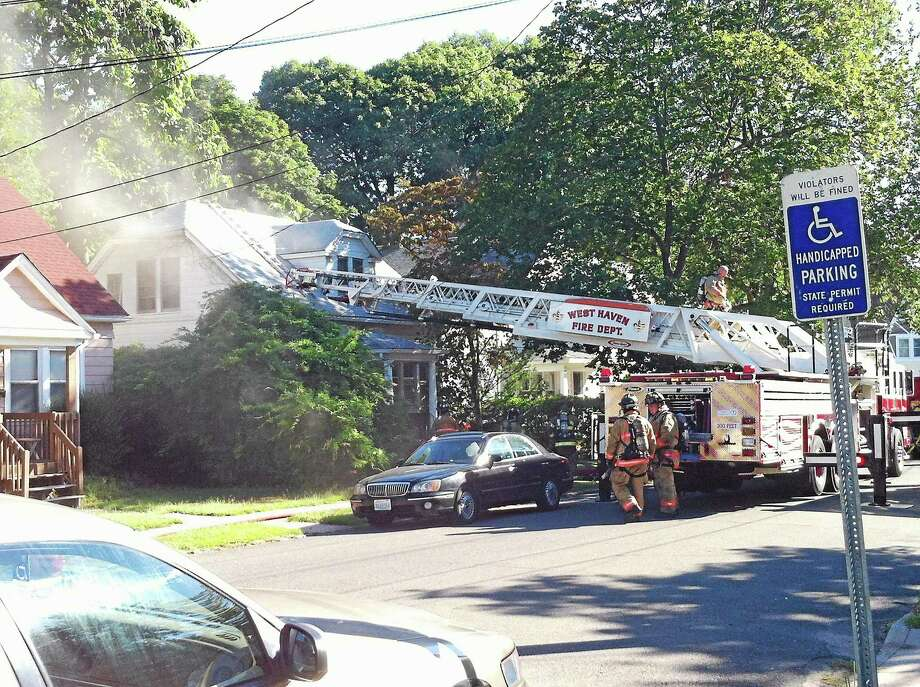 Fire crews quickly put out a smoky basement fire Thursday on Homestead Avenue. A woman inside made it out safely, and one firefighter was being evaluated for an injury. Photo: (Wes Duplantier -- New Haven Register)