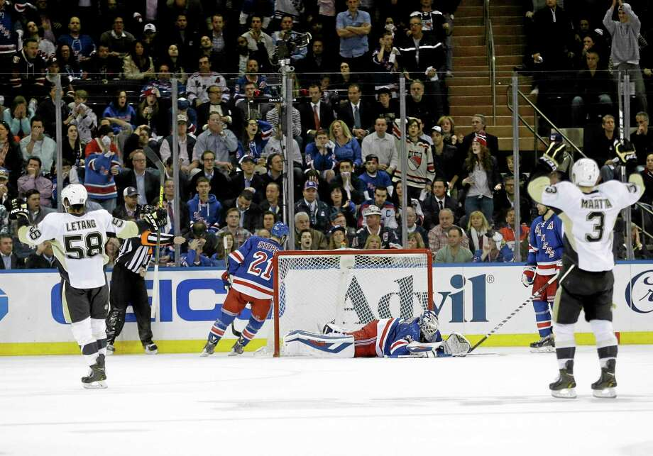 Pittsburgh Penguins' Olli Maatta (3) and Kris Letang (58) celebrate a goal by Brandon Sutter as New York Rangers goalie Henrik Lundqvist, center, reacts during the second period of a second-round NHL Stanley Cup playoff series. Photo: Frank Franklin II  — The Associated Press   / AP