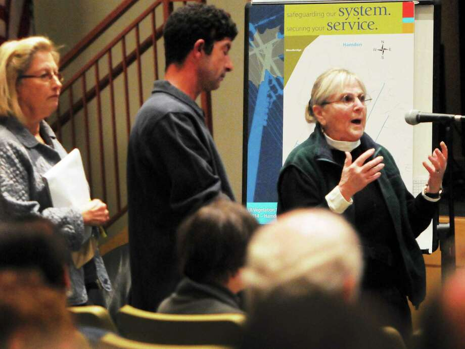 Nancy Alderman, right, a 40-year resident of North Haven and a graduate of the Yale University School of Forestry, responds to Jim Cole of The United Illuminating Co. after he made presentation to area residents during an information session regarding UI's Distribution Vegetation Management Program Wednesday evening in the auditorium of the Hamden Middle School. Photo: Peter Hvizdak — New Haven Register        / ©Peter Hvizdak /  New Haven Register
