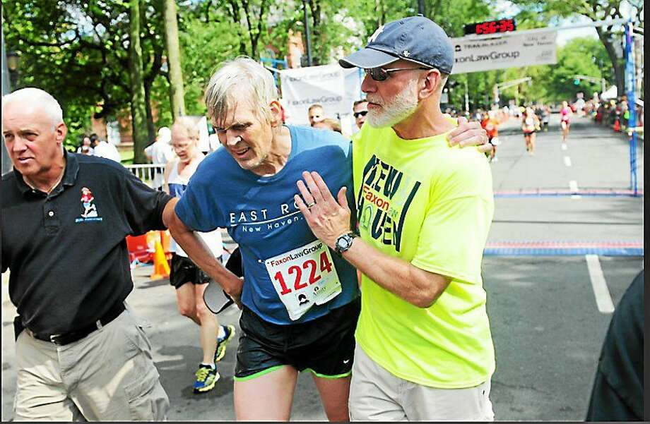 Randall Beach, center, at the finish line of the Faxon Law New Haven Road Race. Photo: (Arnold Gold — New Haven Register)