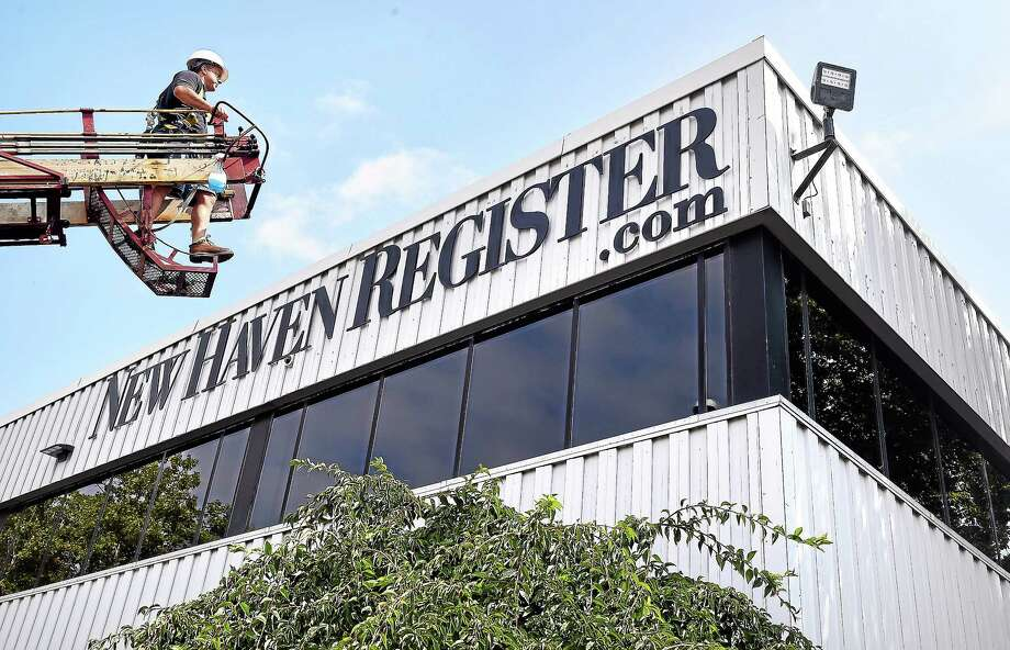 Pete Dayo, owner of New Haven Sign Company, looks over the New Haven Register .com sign he installed at the new location of the New Haven Register at 100 Gando Drive in New Haven on 8/21/2014. Photo: (Arnold Gold-New Haven Register)