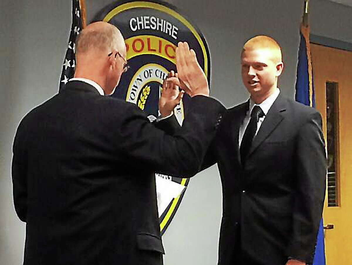 Cheshire's newest police officer, Kyle Pixley, is sworn in by retired probate judge Ray Voelker on Monday morning. Luther Turmelle -- New Haven Register