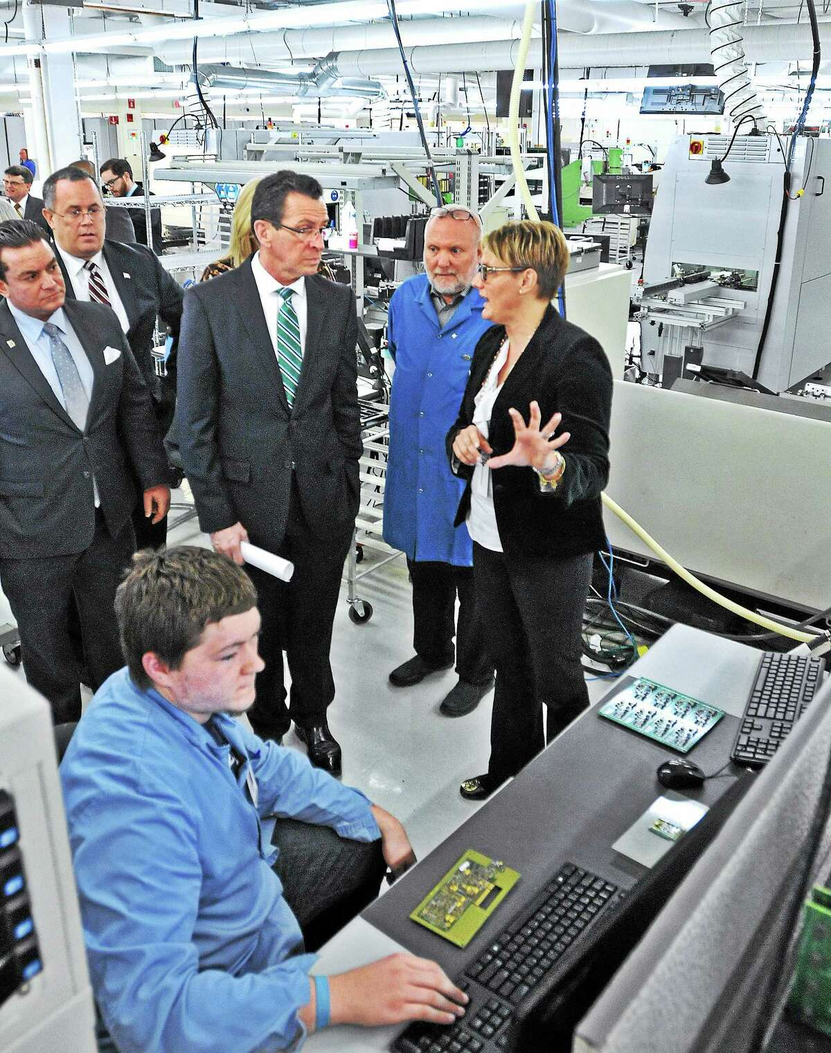 (Peter Casolino-New Haven Register) Governor Dannel P. Malloy gets a tour of Microboard Processing, Inc.(MPI) from the company president Nicole Russo, right, and CEO Craig Hoekenga, second from right. Malloy was at the company to celebrate the state's Small Business Express Program (EXP). MPI is the 1,000th state company that has received assistance through the program. MPI is located in Seymour. March 10, 2014. pcasolino@NewHavenRegister