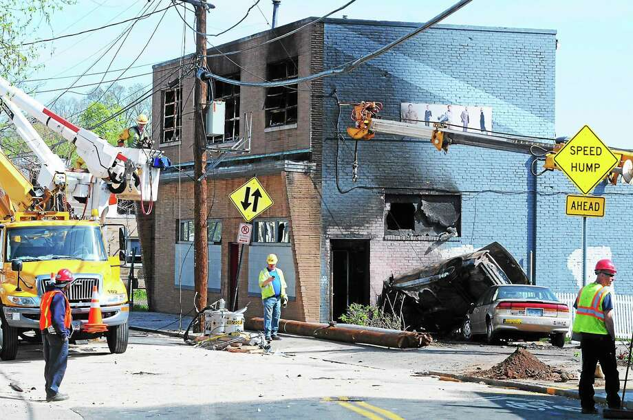A police-involved car chase ended in a crash and fire, damaging power lines on Front Street in New Haven. Photo: ARNOLD GOLD — New Haven Register