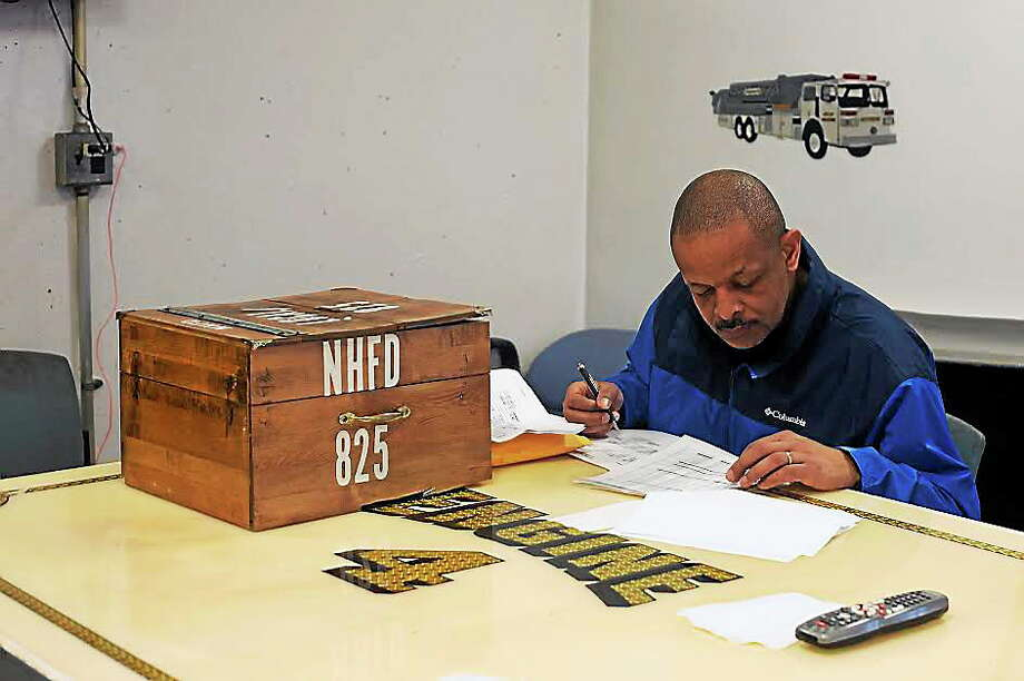 Lt. John Brown sits next to the fire union voting box at fire headquarters and checks names of people who have already voted. Photo: Photo By Rich Scinto/ New Haven Register