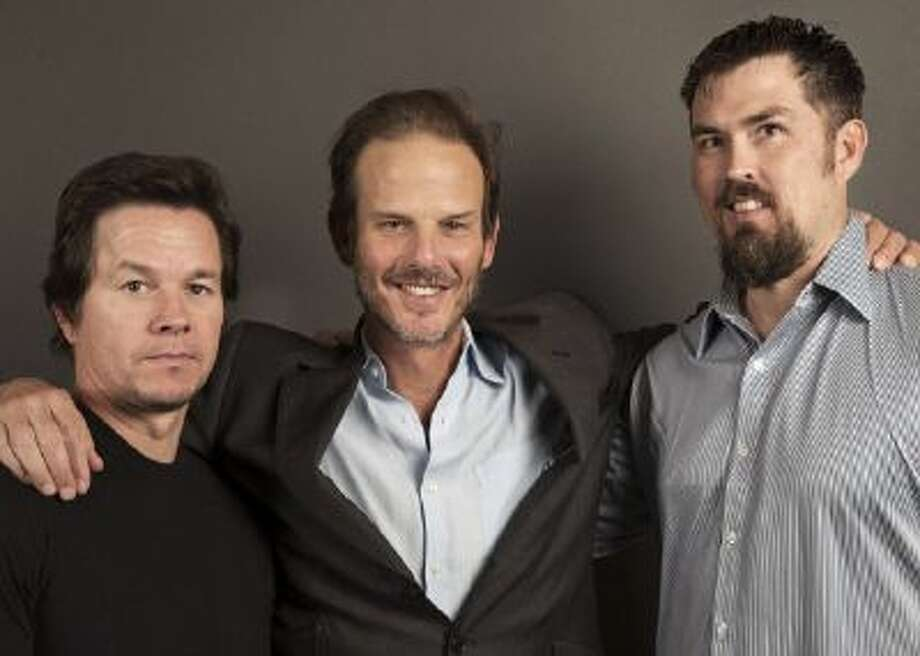 "From Universal's film, ""Lone Survivor"", actor Mark Wahlberg, left, Director Peter Berg, center, and former Navy SEAL and author of the book ""Lone Surivivor,"" Marcus Luttrell, right, pose for a portrait, on Thursday, Dec. 5, 2013 in New York."