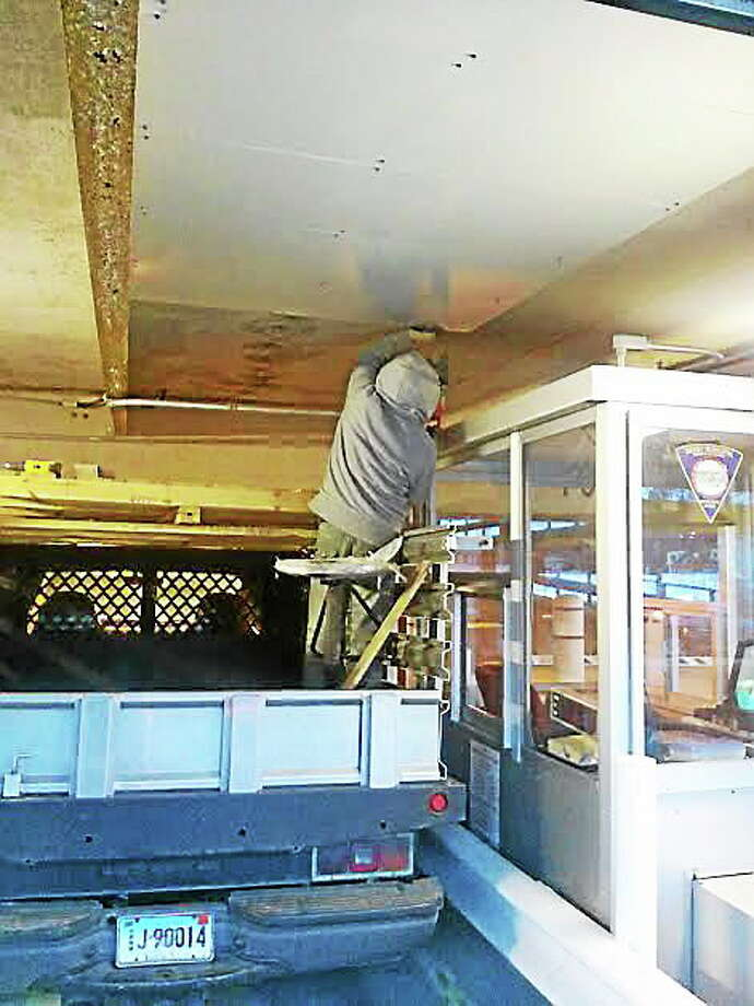 A worker makes repairs to the Derby parking garage. Contributed photo. Photo: Journal Register Co.
