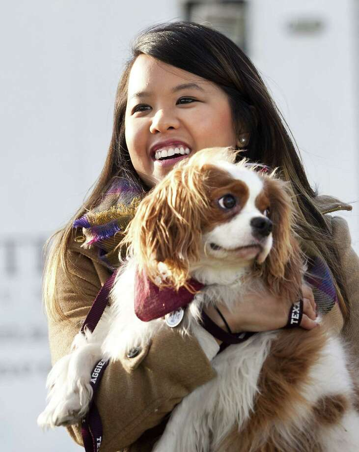 Nina Pham holds up her dog Bentley, at Hensley Field in Grand Prairie, Texas, Nov. 1, 2014. Pham, who recovered from Ebola, and the King Charles Spaniel were reunited privately on Saturday in a vacant residence where officers once lived at a decommissioned naval air base, where he was quarantined for 21 days. Photo: (AP Photo/The Fort Worth Star-Telegram, Juan Guajardo)   / The Fort Worth Star-Telegram
