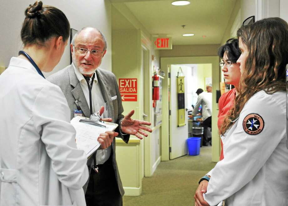 From left, Yale nursing student Allison Whitmer; Dr Steven Wolfson; interpreter Leen VanBesien; and Yale nursing student Taylor McGuinnes confer at the Haven Clinic recently. Photo: (Melanie Stengel — New Haven Register)