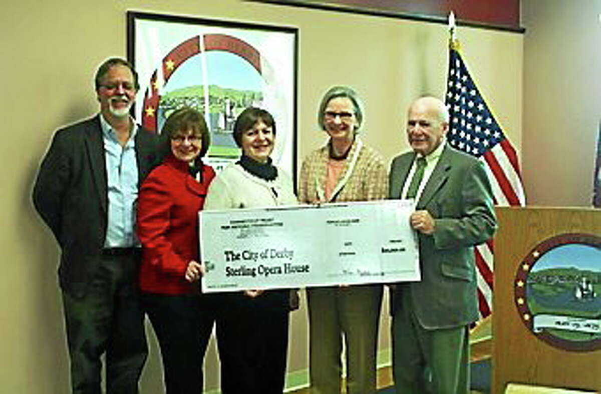 Officials including Mayor Anita Dugatto, center, hold an oversized check for the opera house.