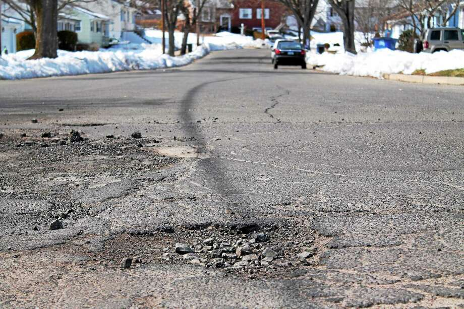 Potholes like this one on Charter Oak Avenue must be filled during cold weather months by substance called cold patch. Overdue bills owed to TilCon Connecticut have prevented the town from receiving its normal purchases, the town instead has had to pay a local hardware store for individual, costlier bags. (Evan Lips - New Haven Register) Photo: Journal Register Co.
