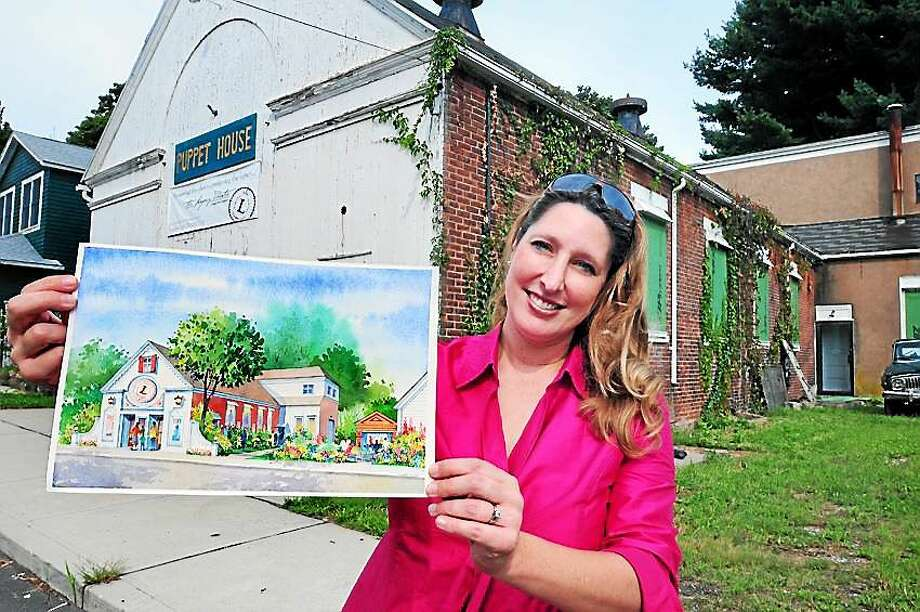 Keely Baisden Knudsen, artistic director of the Legacy Theater, holds an artist's rendering of plans for the former Puppet House (background) in the Stony Creek section of Branford. Photo: Arnold Gold — New Haven Register File Photo