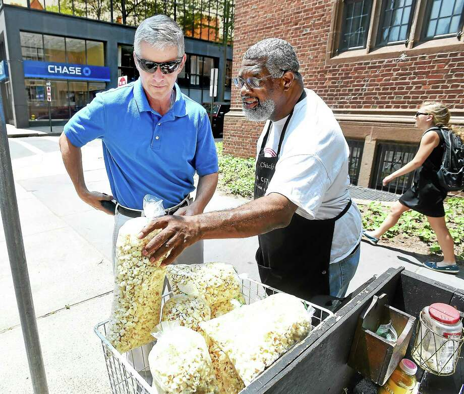 "Jim Brennan, left, of Orange buys kettle corn from Reggie ""Chickie Little"" Simms at the corner of Church and Wall streets in New Haven. Photo: Arnold Gold — New Haven Register"