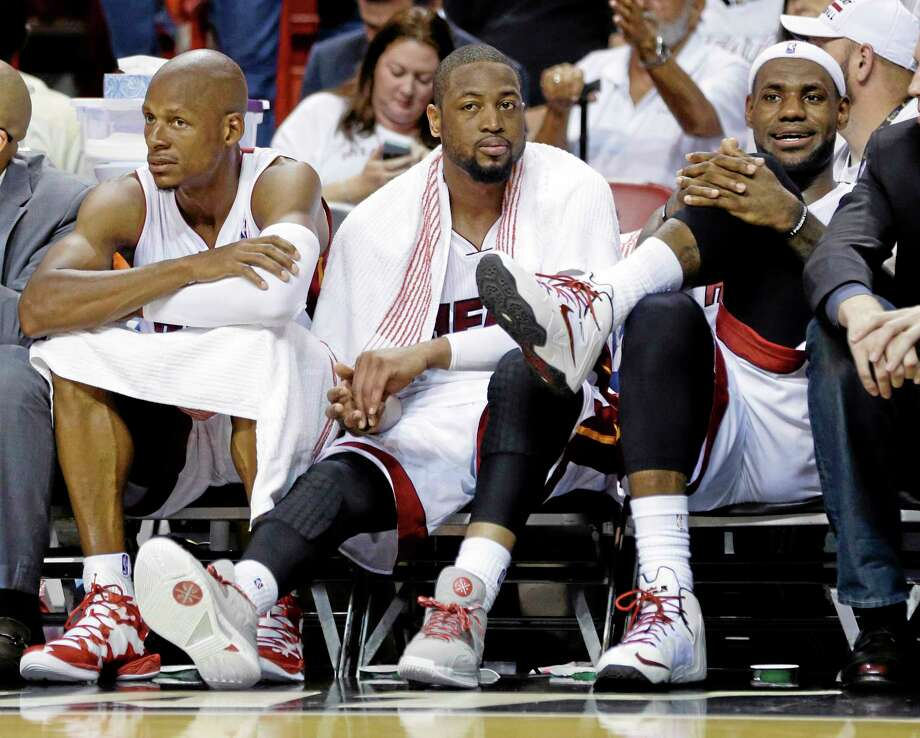 The Heat's Ray Allen, left, Dwyane Wade and LeBron James, right, watch from the bench late in the second half of Game 1 of the NBA Eastern Conference semifinal series against the Brooklyn Nets, Tuesday.The Heat defeated the Nets 107-86. Photo: Lynne Sladky — The Associated Press   / AP
