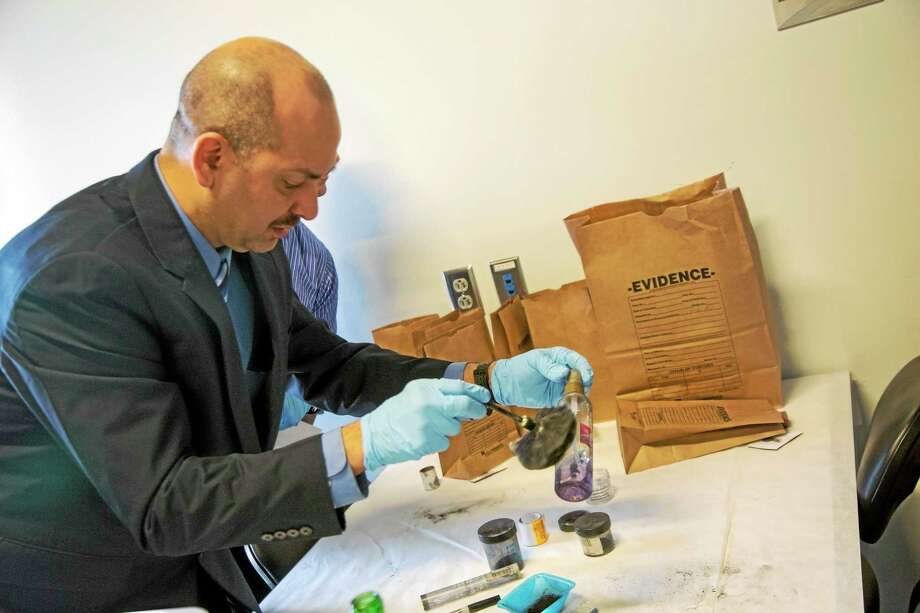 Detective Juan Monzon dusts for prints after he and his team collect potential evidence from a simulated crime scene. Photo by Rich Scinto/ New Haven Register Photo: Journal Register Co.
