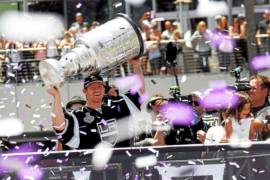 Hamden native and Los Angeles Kings goalie Jonathan Quick holds up the Stanley Cup while riding in a parade in downtown Los Angeles on June 16. Photo: The Associated Press File Photo   / AP2014