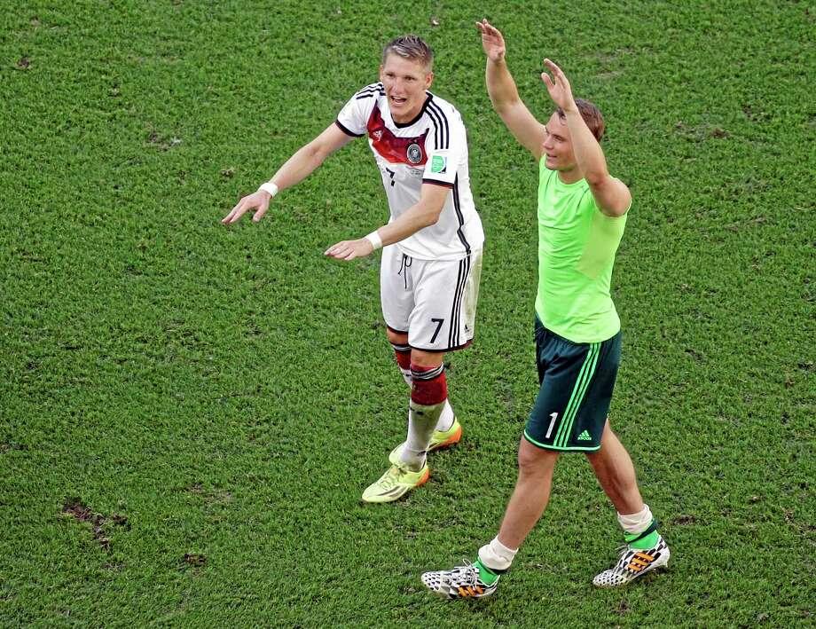 Germany's Bastian Schweinsteiger, left, and Manuel Neuer celebrate after their World Cup quarterfinal win over France Friday at the Maracana Stadium in Rio de Janeiro. Photo: Matt Dunham — The Associated Press   / POOL AP