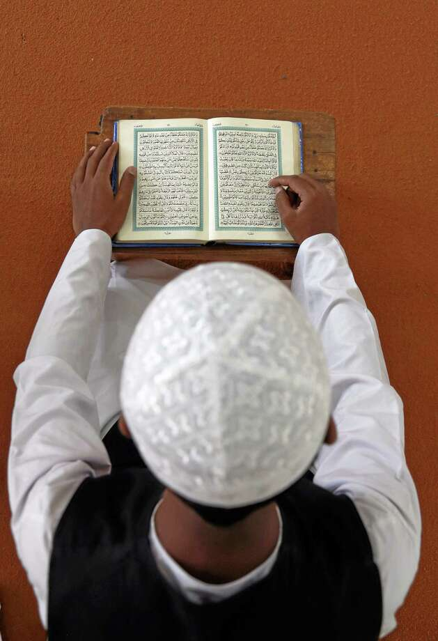 An Indian Muslim boy reads the Quran during the holy month of Ramadan at a madrasa, or religious school, in Hyderabad, India, July 2, 2014. Photo: Mahesh Kumar A. — The Associated Press   / AP