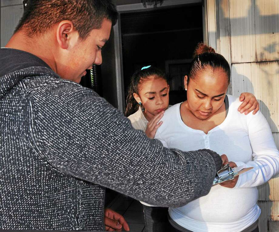 Volunteer canvasser Junior Sierra of Norwalk, left, talks with Keyla Diaz, 12, and her mother, Keyla Mendoza, during a neighborhood canvass Tuesday in New Haven. The canvas targeted middle school students and their parents; volunteers distributed information packets and stressed the importance of good school attendance. Photo: Melanie Stengel — New Haven Register