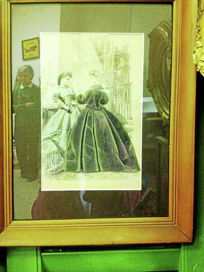 Modern and historical: A view of a piece of art at the Orange Historical Society's Academy building that also reflects folks in the society's gift shop on Orange Center Road, across from the town Green Photo: Journal Register Co.