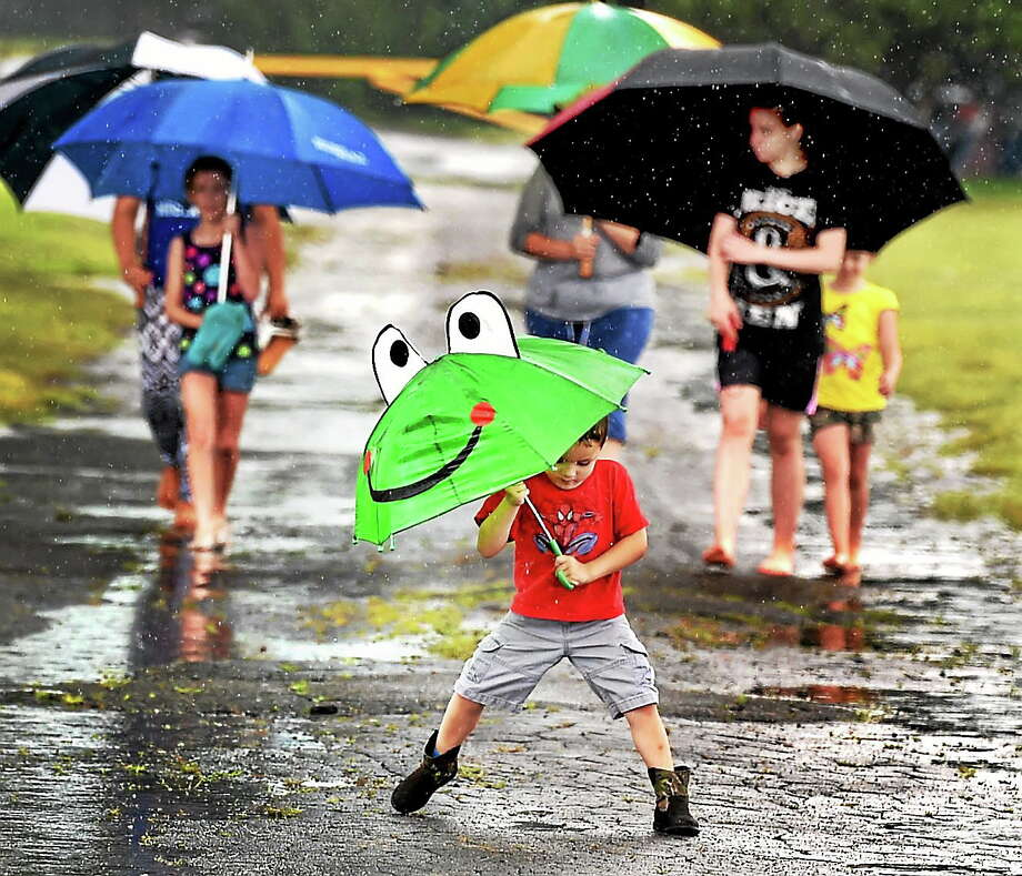 Three-year-old Aiden Dart of Chicopee, Massachusetts, plays in the puddles as he and his family take a walk at Hammonasset Beach State Park in Madison Friday. Though the weather changed many people's Fourth of July plans, folks still found ways to celebrate the day. The extended Dart family camps at Hammonasset several times a year. Photo: (Mara Lavitt — New Haven Register)     / Mara Lavitt