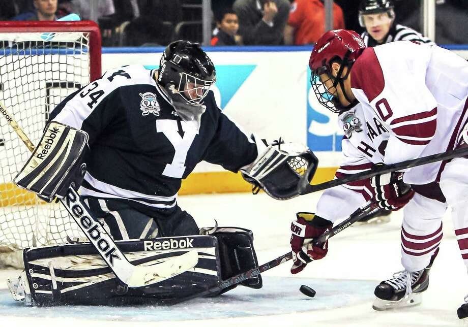 Yale goaltender Alex Lyon makes a save on a shot by Harvard forward Brayden Jaw during the 10th-ranked Bulldogs' 5-1 win on Saturday night at Madison Square Garden in New York. Photo: John Vanacore — Special To The Register   / JOHN VANACORE/NEW HAVEN REGISTER