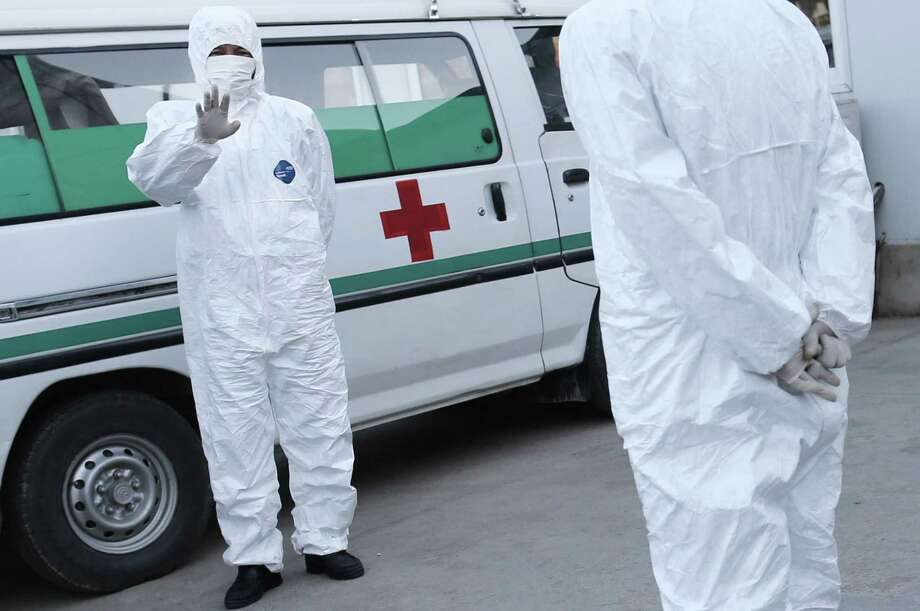 This Monday, Oct. 27, 2014 photo shows medical personnel in protective suits standing by an ambulance, at the Sunan International Airport, in Pyongyang, North Korea. North Korea would seem like the last place on Earth that has anything to worry about from Ebola. But it's virtually gone on DefCon 1 over what it sees as a looming invasion from the outside world that threatens to infiltrate its borders and relentlessly attack its people unless dramatic measures are taken immediately. It has banned tourists, put business groups on hold and is looking even more suspiciously than usual at every foreign face coming across its borders. (AP Photo/Wong Maye-E) Photo: AP / AP