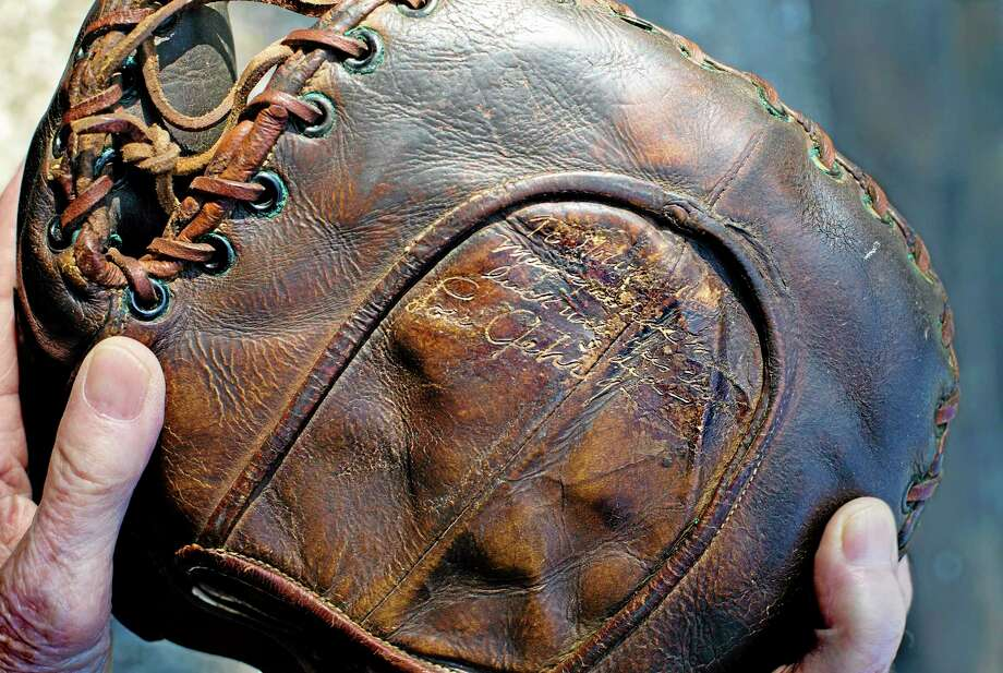 Howard Henderson, who as a boy in New York played catch with baseball legend Lou Gehrig, holds a signed baseman's mitt given to him by Gehrig when he was young, at Henderson's home Monday in Greenwich. Gehrig, a Yankee first baseman and a friend of Henderson's songwriter father, visited his home and Henderson visited him when he had ALS. The mitt that was autographed by Gehrig with a hot instrument, will be auctioned in July, expecting to fetch $200,000 to $300,000. Photo: Associated Press   / FR61802 AP
