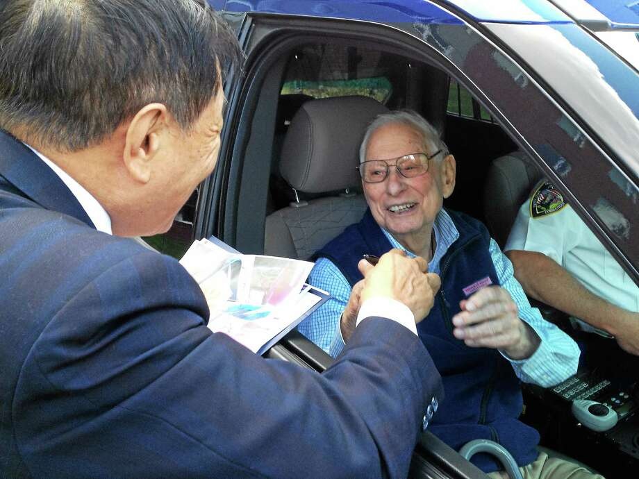 "Henry C. Lee, founder of the Henry C. Lee Institute of Forensic Science at UNH, delivers gifts to Joseph E. ""Chick"" Celentano. Photo: Mark Zaretsky — New Haven Register"