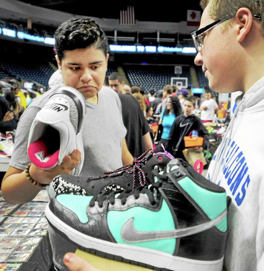 Gilbert Becerra, 16, of Port Chester, N.Y., left, examines a hard-to-get Nike basketball shoe that Joe Conveertitio, 14, of Shelton, is trying to sell Sunday on the floor of the Connecticut Sneaker Show at the Webster Arena in Bridgeport. Photo: Peter Hvizdak — Register   / ©Peter Hvizdak /  New Haven Register