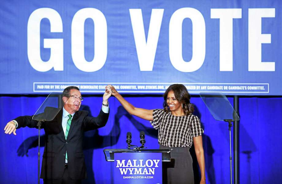 (Arnold Gold-New Haven Register)  Governor Dannel Malloy (left) and First Lady Michelle Obama wave to the crowd during a campaign appearance for the governor at Wilbur Cross High School in New Haven on 10/30/2014. Photo: Journal Register Co.