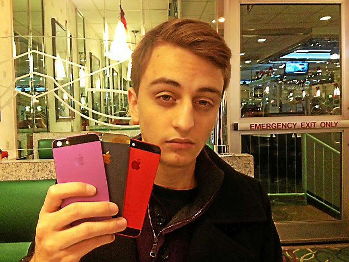 Brandon Connor holding up samples of the colored device casings his company makes.