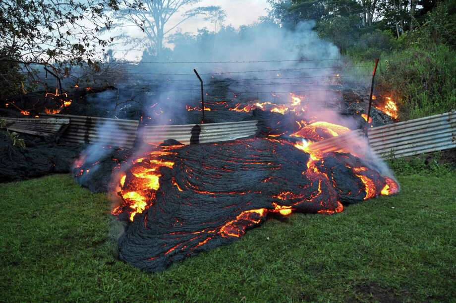 This Tuesday, Oct. 28, 2014 photo provided by the U.S. Geological Survey shows lava that has pushed through a fence marking a property boundary above the town of Pahoa on the Big Island of Hawaii. After weeks of slow, stop-and-go movement, a river of asphalt-black lava was less than the length of a football field from homes in the Big Island community Tuesday. The lava flow easily burned down an empty shed at about 7:30 a.m., several hours after entering a residential property in Pahoa Village, said Hawaii County Civil Defense Director Darryl Oliveira. A branch of the molten stream was less than 100 yards (90 meters) from a two-story house. It could hit the home later Tuesday if it continues on its current path, Oliveira estimated. Residents of Pahoa Village, the commercial center of the island's rural Puna district south of Hilo, have had weeks to prepare for what's been described as a slow-motion disaster. Most have either already left or are prepared to go. (AP Photo/U.S. Geological Survey) Photo: AP / U.S. Geological Survey
