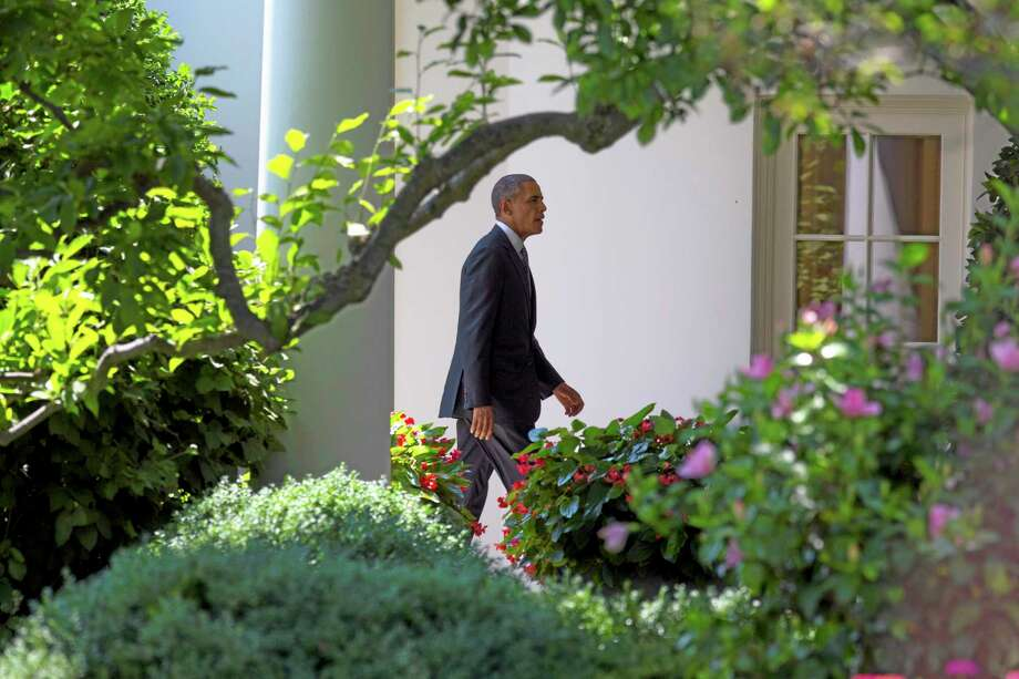 President Barack Obama walks to the Oval Office of the White House in Washington, Friday, June 27, 2014, after arriving on the South Lawn, from a trip to Minnesota. (AP Photo/ Evan Vucci) Photo: AP / AP