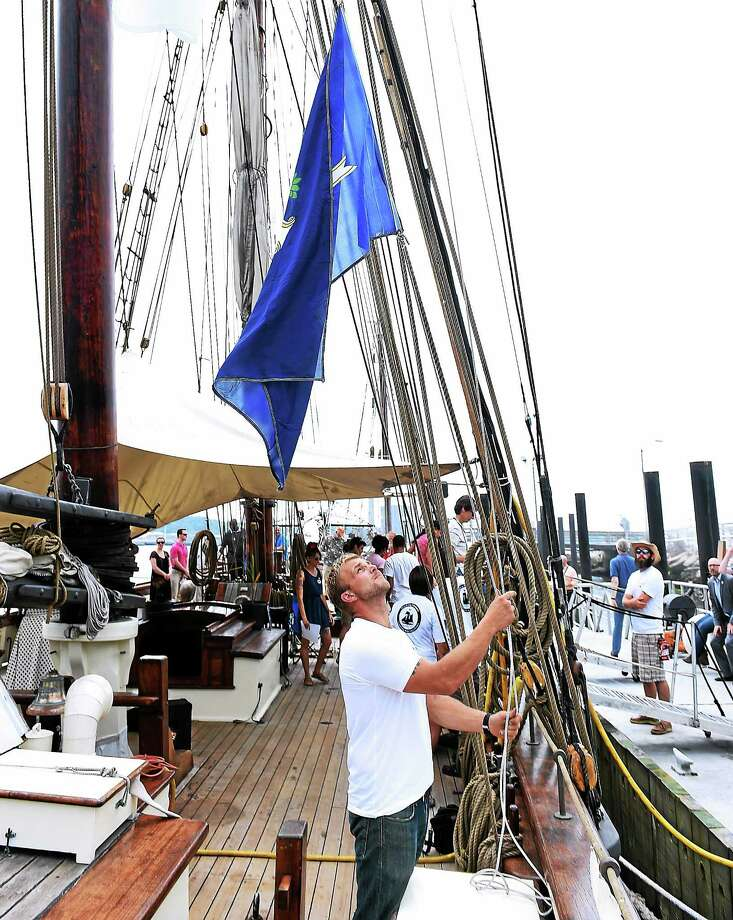 Jesse Doucette, chief officer on the Freedom Schooner Amistad, raises the Connecticut flag during the boat's homecoming ceremony Wednesday in New Haven. Photo: Peter Casolino — New Haven Register
