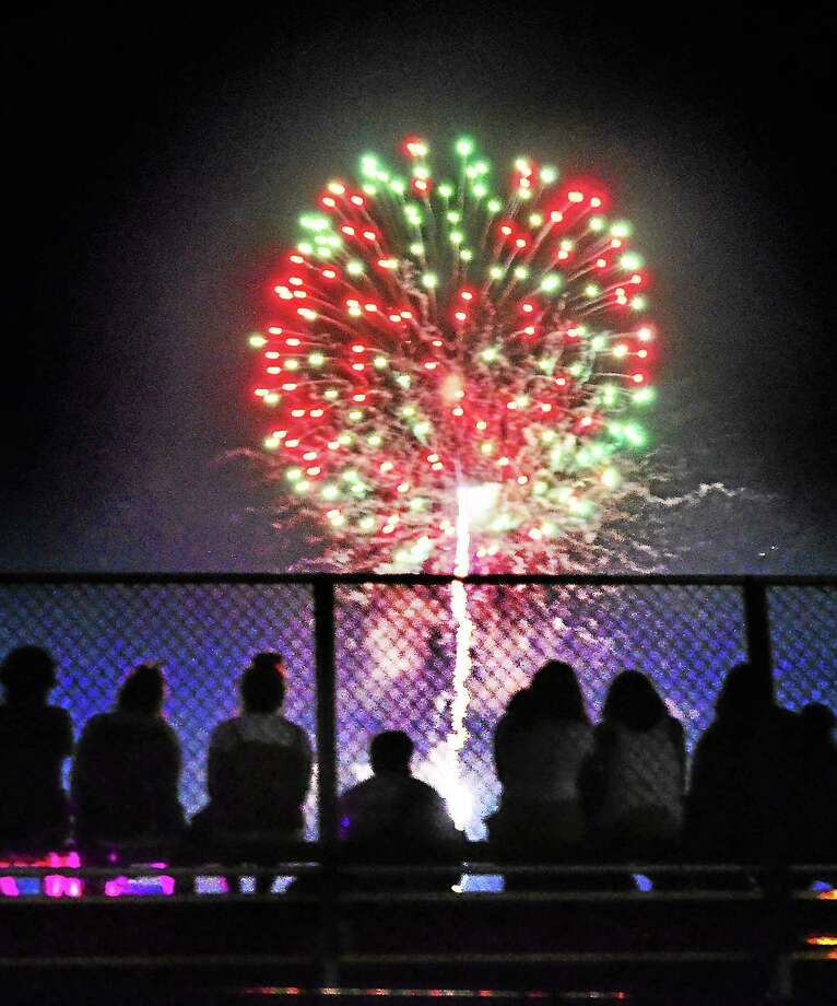 People watch the New Haven fireworks from the bleachers at the Wilbur Cross football field in 2013. Photo: Melanie Stengel — NEW Haven Register File Photo