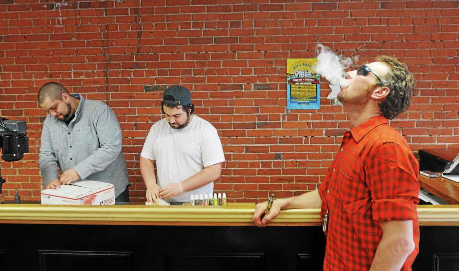 """Customer Raymond Vickers of West Haven enjoys some """"vape"""" as he hangs out in the lounge area of White Buffalo Vape shop. Employee Nick Anderson, left, and co-owner Noah Morgenstein organize a new shipment of products. Photo: Peter Casolino-New Haven Register"""