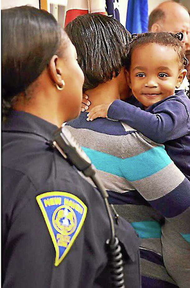 File photo: Tramire Miller, then 16 months, of New Haven, smiles at Officer Jillian Knox during a press conference at police headquarters. The toddler was shot in the stomach and recovered. Photo: Melanie Stengel/New Haven Register