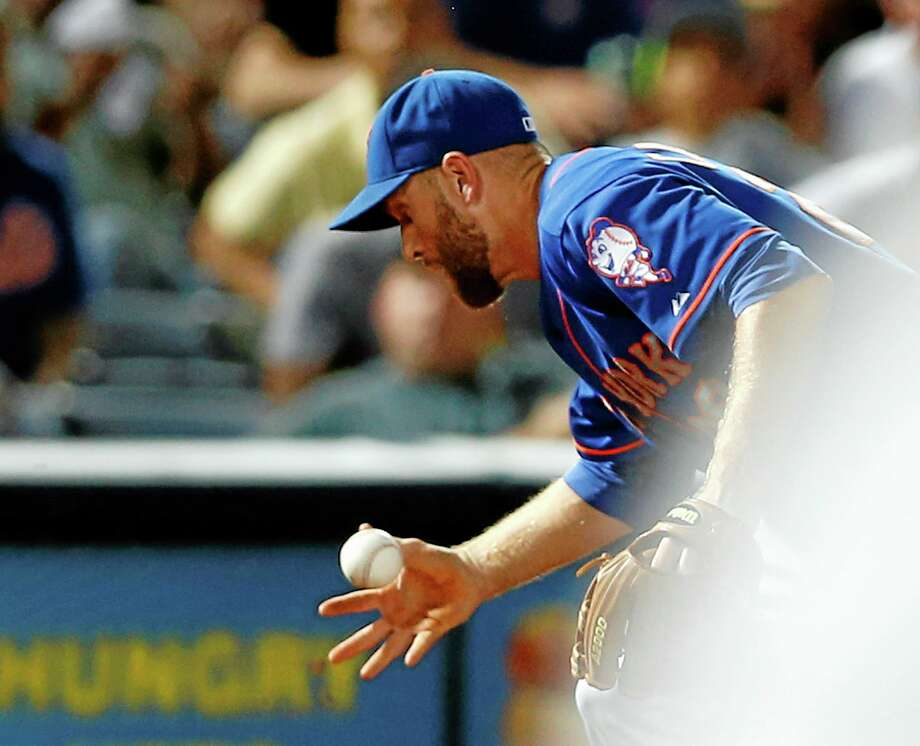 Mets third baseman Eric Campbell (29) has trouble fielding a ball hit by Atlanta Braves' Andrelton Simmons in the eighth inning Monday. The go-ahead run scored on the play and Campbell was charged with an error. Atlanta won 5-3. Photo: John Bazemore  — The Associated Press   / AP