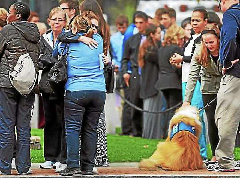 Two women hug, left, and a therapy dog does his job, right, as people wait in at the Cody-White Funeral Home on North Broad Street in Milford Thursday during the wake for Maren Sanchez. Peter Hvizdak ó New Haven Register Photo: Journal Register Co.