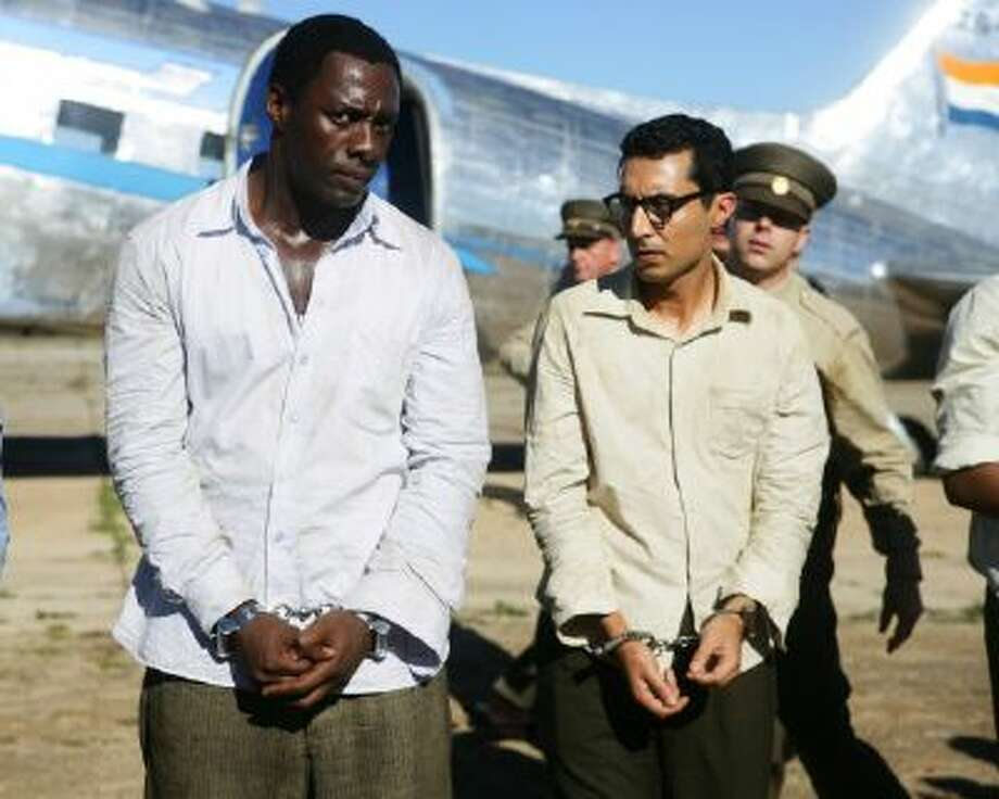 """This photo released by The Weinstein Company shows Idris Elba, left, as Nelson Mandela, and Riaad Moosa, as Ahmed Kathrada, in the film, """"Mandela: Long Walk to Freedom."""""""
