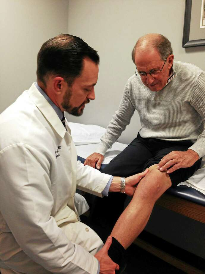 Dr. Aaron Schachter examines the knee replacement he performed on Paul Kuhn of Farmington. (Ed Stannard — New Haven Register) Photo: Journal Register Co.