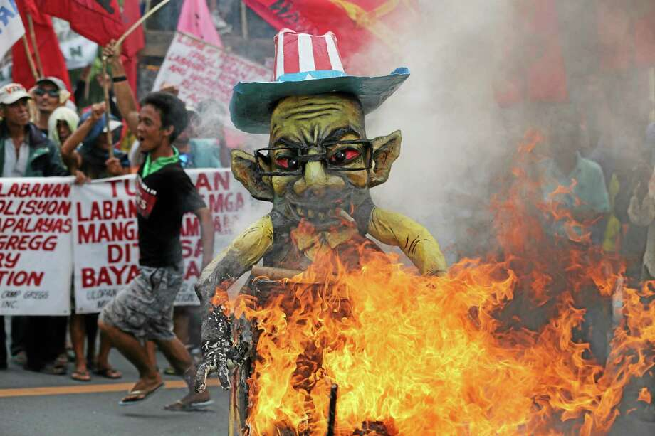 A Filipino activist runs beside a burning effigy of Philippine President Benigno Aquino III as protesters try to get near his house.  His stance on agrarian issues has also made him unpopular with farmers. Photo: AP Photo — Aaron Favila    / AP