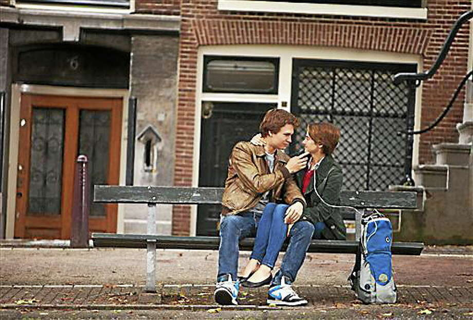 """FILE - In this file image released by 20th Century Fox, Ansel Elgort, left, and Shailene Woodley appear in a scene from """"The Fault In Our Stars."""" The city of Amsterdam isn't quite sure whether to blame fate or human error, but a bench upon which the star-crossed teenage lovers talk and kiss in the hit film """"The Fault in Our Stars"""" is missing. The green bench that used to sit on the Leidsdegracht resembles hundreds of others around the city, and its absence went unnoticed for at least a month ? probably because unknown persons placed a large flower pot on the spot. (AP Photo/20th Century Fox, James Bridges, File) Photo: AP / 20th Century Fox"""