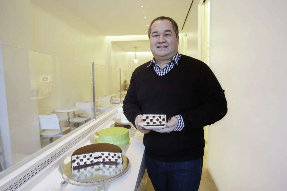 In this Dec. 17, 2014 photo, Ken Romaniszyn, owner of Lady M Cake Boutique, poses for a photo while holding a slice of his Checkers cake, at one of his New York shops. Photo: AP Photo/Mark Lennihan   / AP