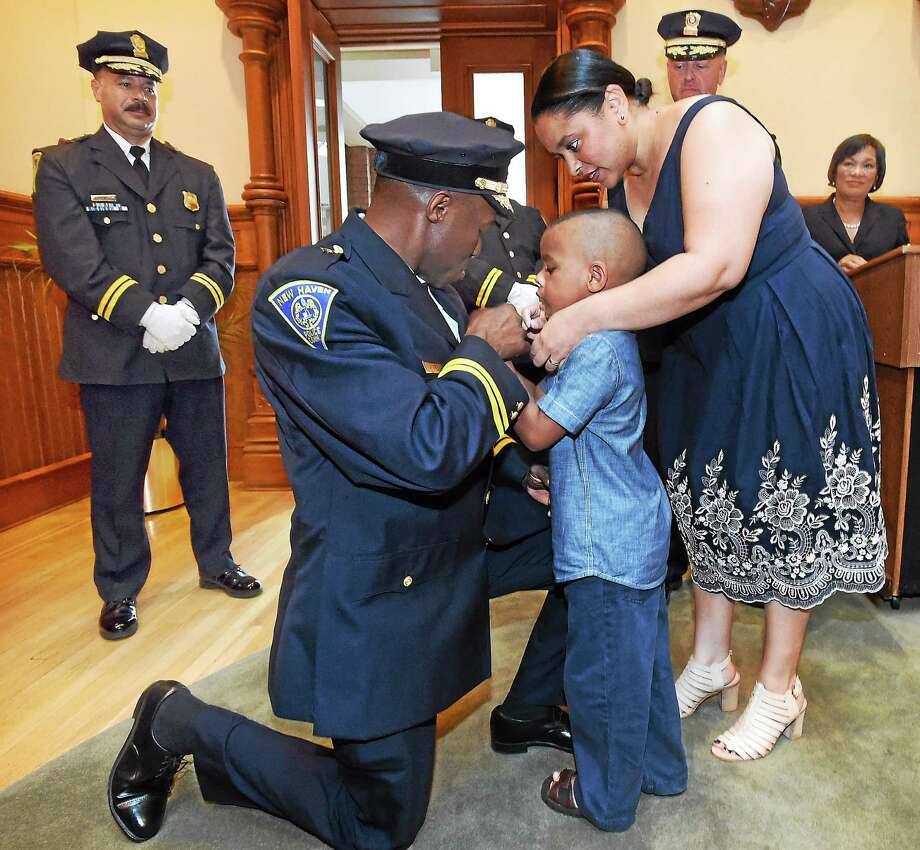 A ceremony was held at New Haven City Hall to swear in two new New Haven assistant chiefs of police: Al Vazquez and Anthony Campbell, shown here getting his badge pinned on by son Paxon age 5 and wife Stephanie. Photo: Mara Lavitt - New Haven Register   / Mara Lavitt